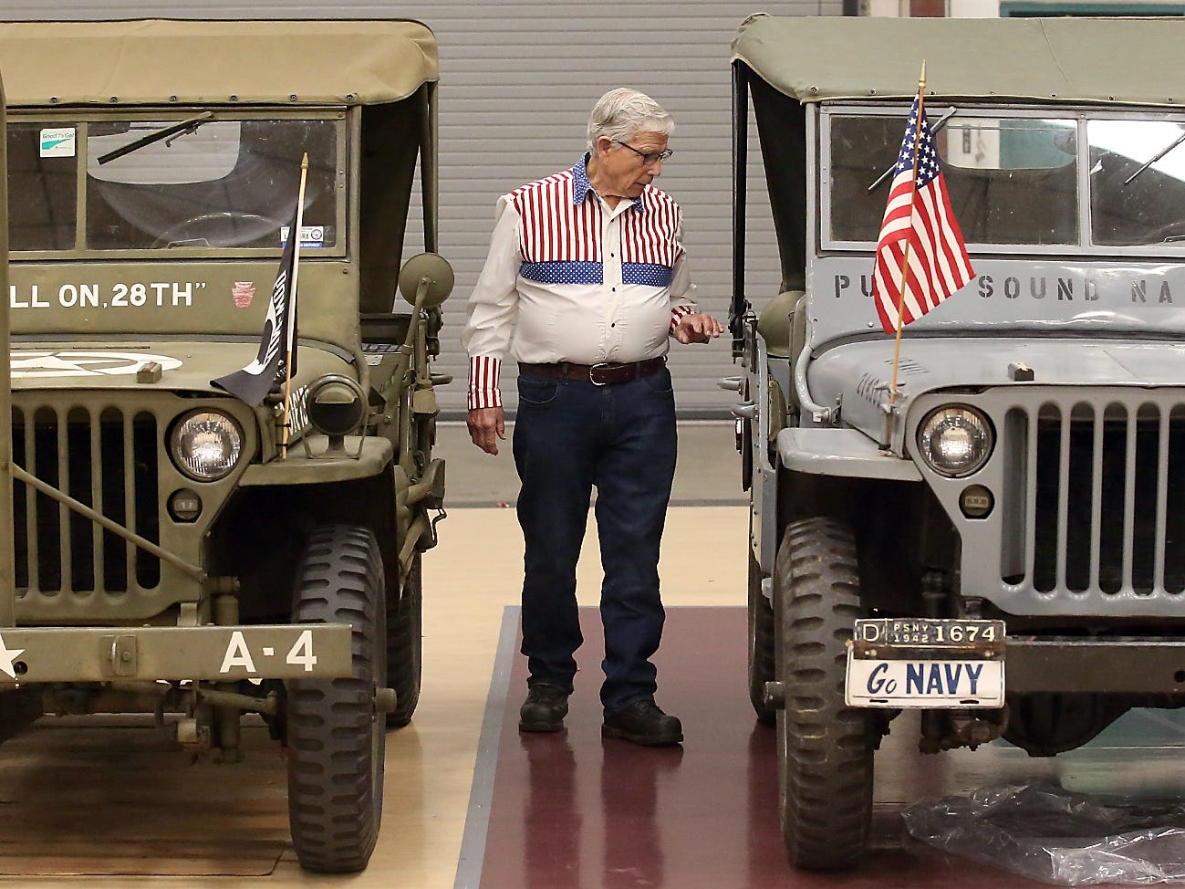 Wearing a patriotic shirt that he made himself, Paul Buckner, of Seabeck, looks over a pair of jeeps on display during the Honoring All Who Served Veterans Day ceremony at the Kitsap Sun Pavilion on Monday, November 12, 2018.
