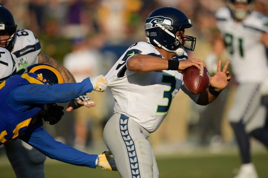 Seattle Seahawks quarterback Russell Wilson passes under pressure from Los Angeles Rams outside linebacker Samson Ebukam.