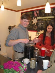 Co-owner of Dynamite Roasting Co., Andy Gibbon, scoops coffee beans during the grand opening party for the business in 2008.