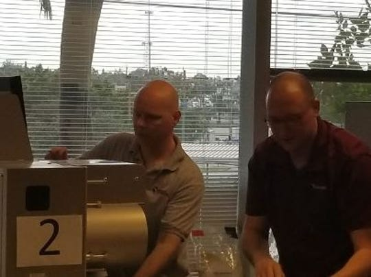 Todd Putnam and Adam Smith assemble ballots during a voting recount in the Lee County Election Supervisor's office Tuesday.