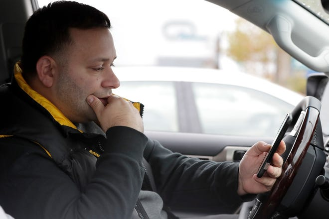 Lenny Sciascia ponders as he looks at betting lines for the day's sporting events before placing his bet in a parking lot just off the Bayonne Bridge, which divides New York and New Jersey. Sciascia, who lives in Staten Island, N.Y., commutes regularly to places his bets from New Jersey, where online betting is legal.
