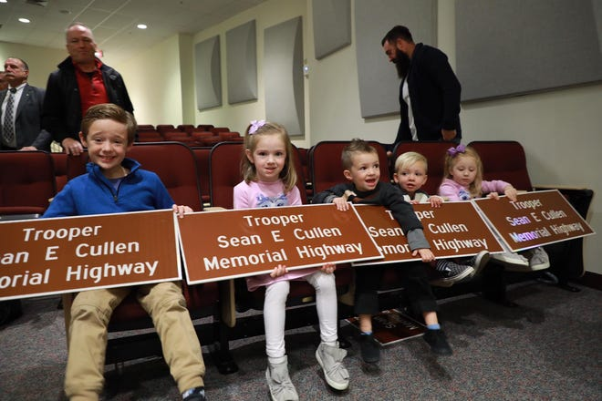 Young family members of fallen trooper Sean Cullen display signs at a ceremony to name a portion of I-295 for the South Jersey officer who was killed in a 2016 line-of-duty accident.