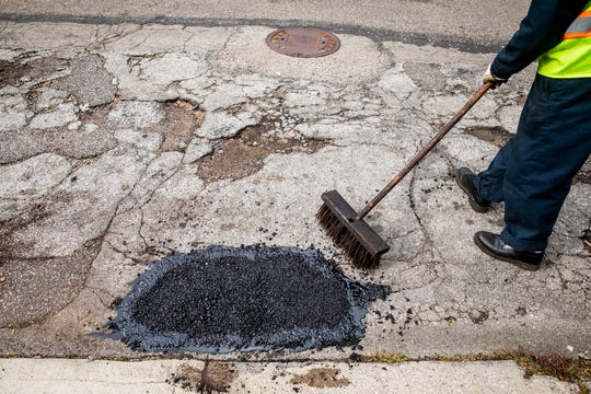 Wilbur Beverly, a Cincinnati Public Services truck driver, sweeps loose gravel onto fresh tar so it won't stick to tires while it dries on Mad Anthony Street in South Cumminsville Wednesday, November 7, 2018.