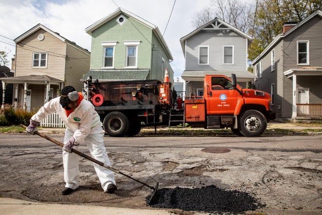 Lucretia Hicks, a Cincinnati Public Services truck driver, fills a pothole on Mad Anthony Street Wednesday, November 7, 2018.