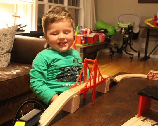 Oliver Schaper, whose diagnosis of spinal muscular atrophy at 14 months explained his loss of movement, plays with his toy trains while in his wheelchair after a lifesaving treatment helped restore strength in the young boy.
