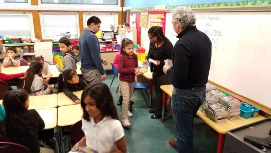 Rotary Club members Aturo Cousar and Timothy Priano (right) present dictionaries to third grade students at Cook Elementary School in Plainfield.