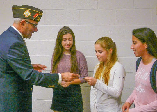 William Testa of the Frenchtown-Milford VFW came to Delaware Valley High School on Nov. 2 to distribute a $900 purse among the winners of the Voice of Democracy speech contest. They are (from left) Nicole Planer, Clare Erwin and Karla Jenkins.