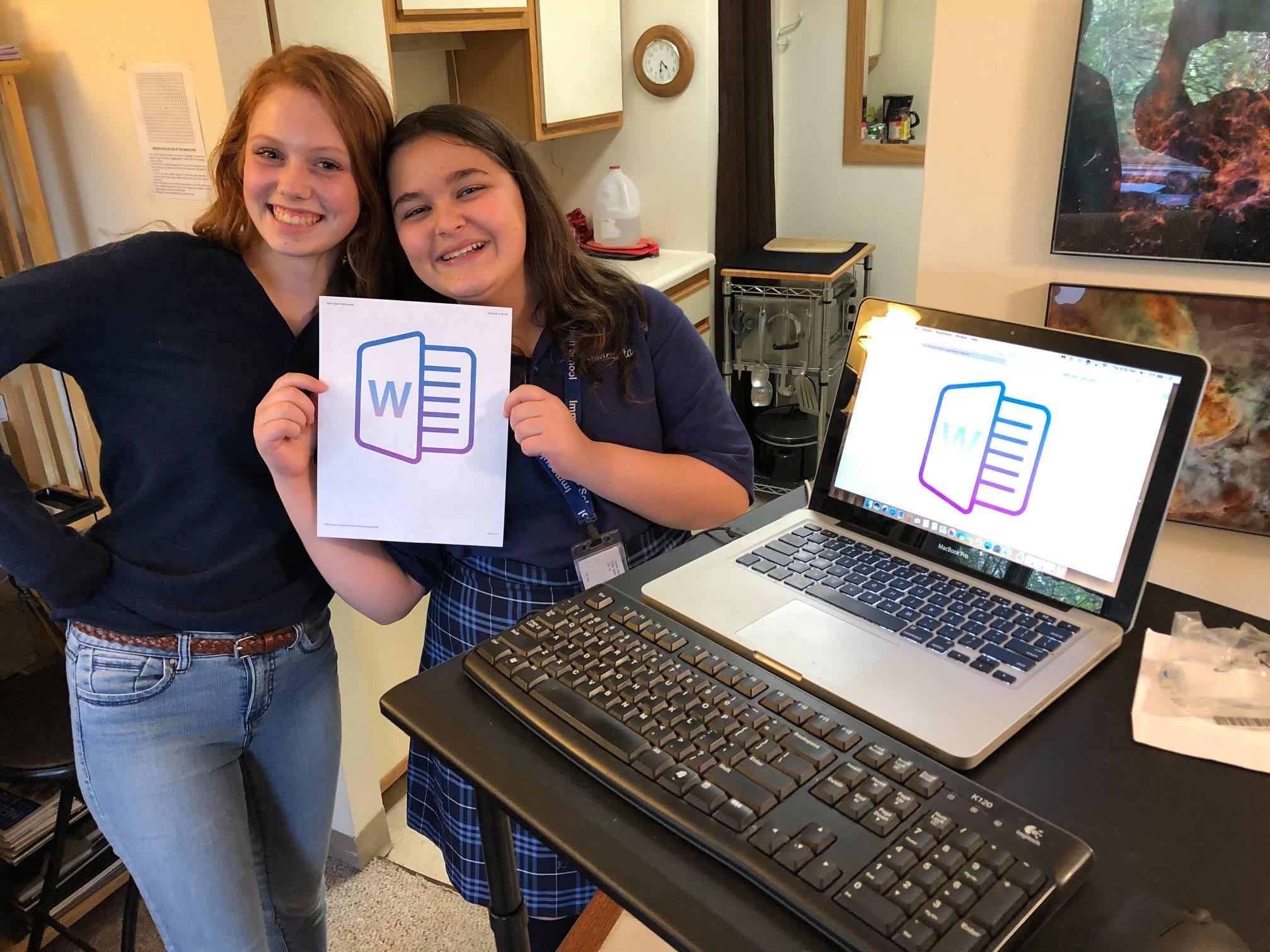 Isabelle LaRoche and Sydney Jaderlund work on computers.