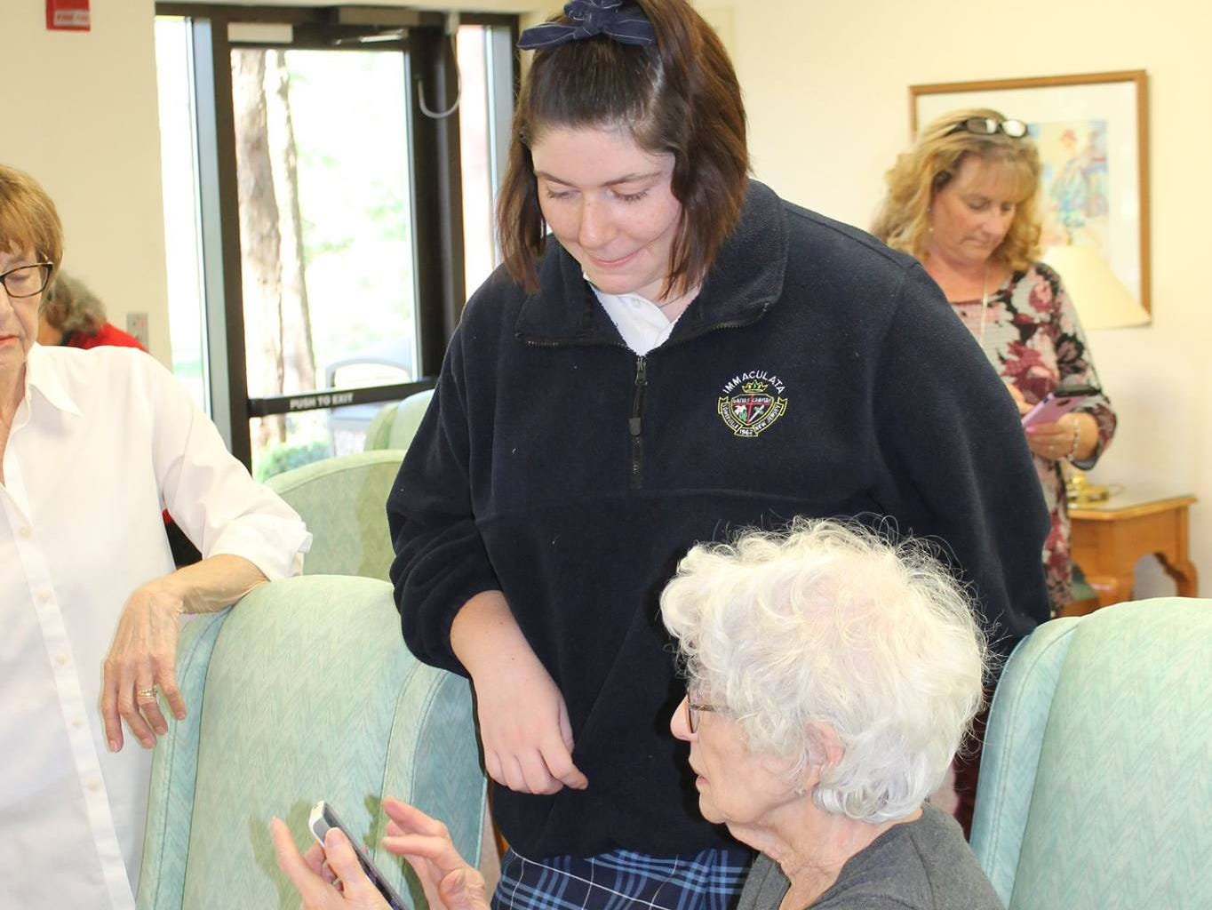 Kate McHale helps a Centerbridge II resident with her phone.