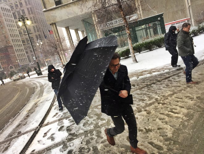 People protect themselves from the falling snow as they walk downtown Detroit on Thursday, March 1st, 2018.