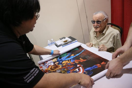 Stan Lee, former president and chairman of Marvel Comics, signs autographs for Jim Yee, 45, of Farmington Hills at the Motor City Comic Con 2013 at Suburban Collection Showplace in Novi, Mich. on Saturday, May 18, 2013. Kimberly P. Mitchell/Detroit Free Press