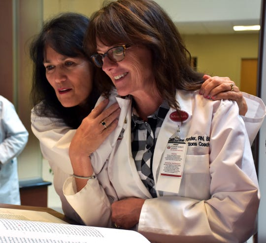 Michelle Moccia, director of the Senior ER and Cathy Ponder, transition team lead, view The Saint John's Bible at St. Mary Mercy Livonia during the weekly page turning.