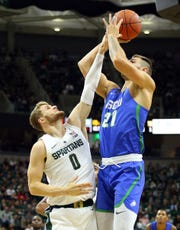 Florida Gulf Coast forward Brady Ernst shoots over Michigan State forward Kyle Ahrens during the first half at the Breslin Center, Nov. 11, 2018 in East Lansing.