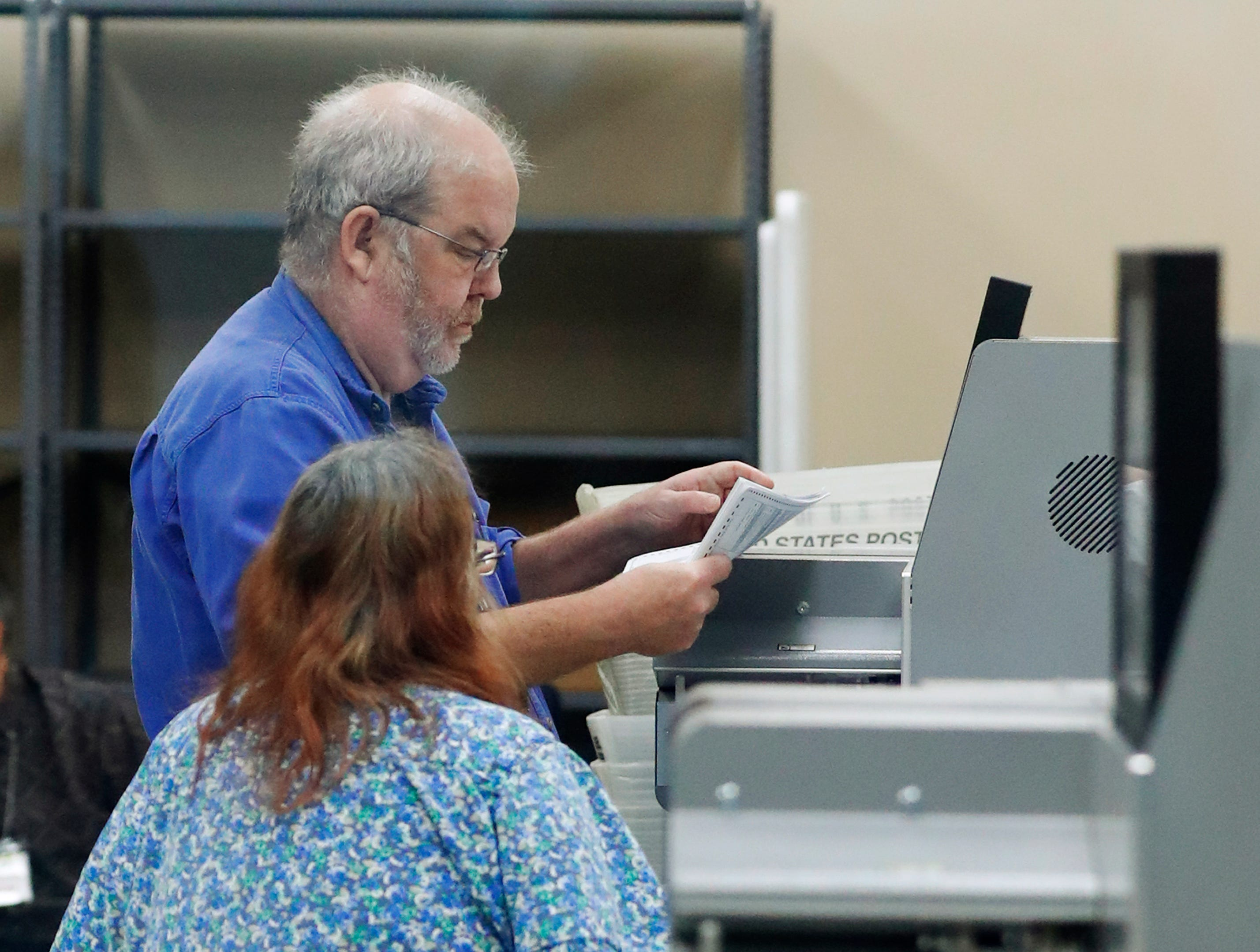 Employees at the Broward County Supervisor of Elections office calibrate machines before counting ballots, Monday, Nov. 12, 2018, in Lauderhill, Fla. Mishaps, protests and litigation are overshadowing the vote recount in Florida's pivotal races for governor and Senate, reviving memories of the 2000 presidential fiasco in the premier political battleground state.