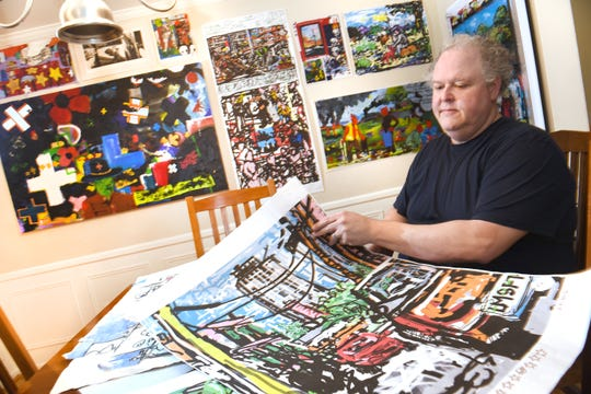Sutton pages through his art portfolio on his dining room table. The onetime pipefitter and estimator both paints and works in digital art.