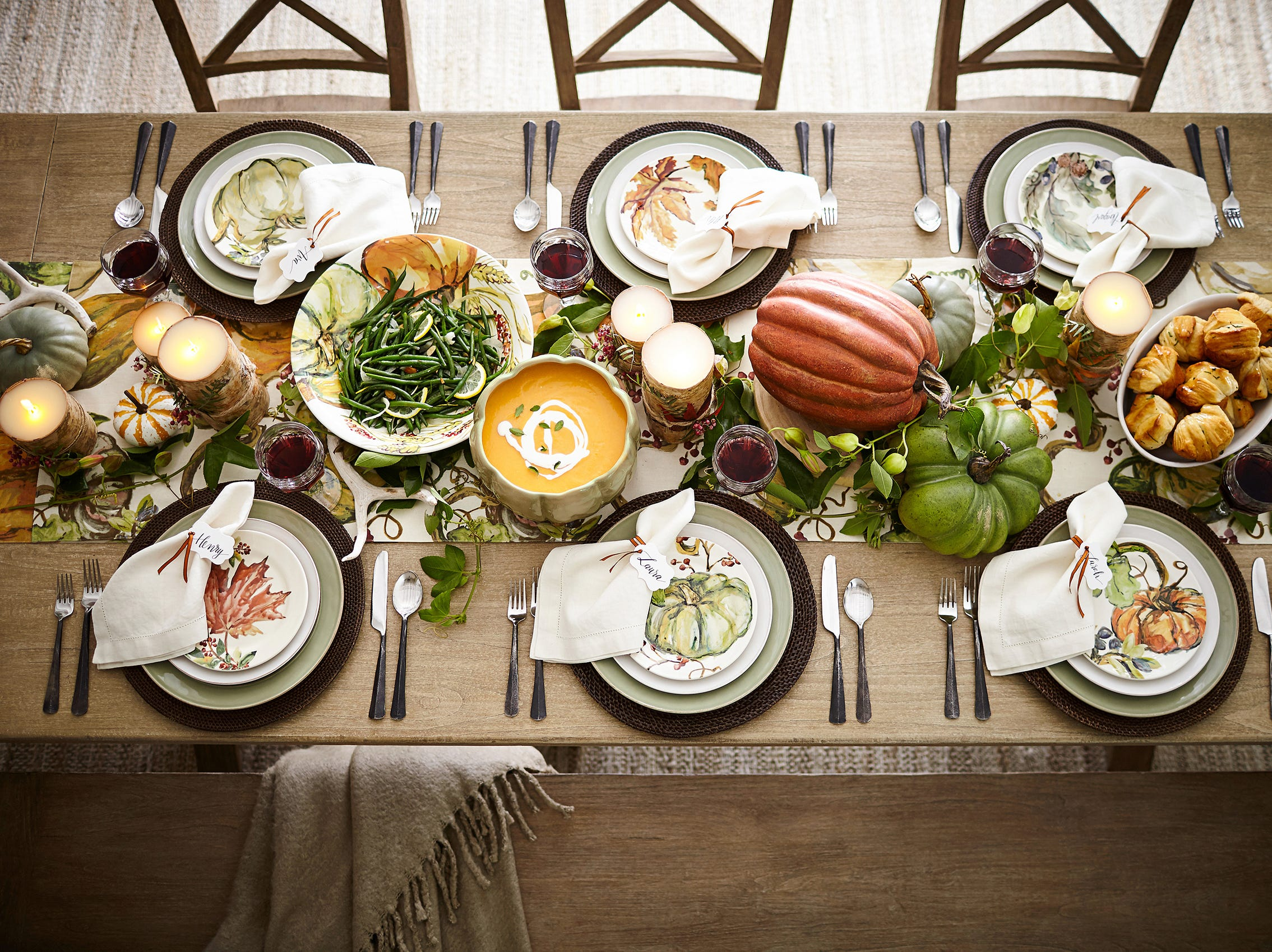 The simplicity of this table shows how pattern (used as a punctuation) and seasonal colors, as well as those of the foods plated, create a dynamic energy. Pumpkin and leaf motifs in soft russets and greens in Harvest Pumpkin and Watercolor Leaf plates are from Pottery Barn. The motifs, drawn from original watercolors, decorate glazed ironstone. They sit on celadon Cambria stoneware plates with hand-applied patina and sprayed glaze, on top of Tava round woven rattan place mats in espresso (honey and natural also available). Ridge flatware is 18/8 stainless steel finished with a richly distressed dark patina and gleaming tips for a modern look. On the Harvest Pumpkin table runner, patterned orange and green pumpkins mingle with serving bowls filled with green beans, pumpkin soup and caramel dinner rolls, each of which adds its own appetizing color.