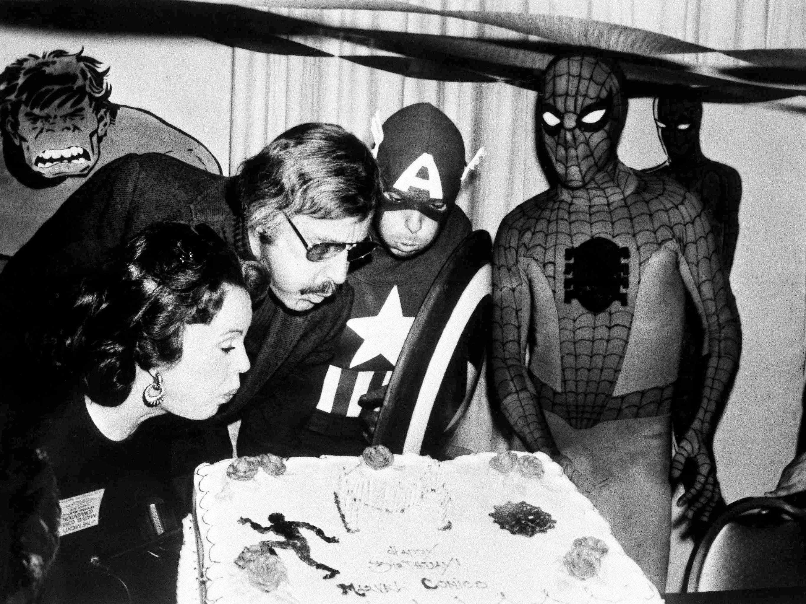 Mighty Marvel comic book publisher Stan Lee, center left, blows out the candles on the Marvel Comics birthday cake at opening day ceremonies of the First Mighty Marvel Comic Book Convention, March 22, 1975, in New York. At left is Lee's wife Joan and on the far right, Spider-Man. Another Marvel Superhero, Captain America, looks on from the rear.