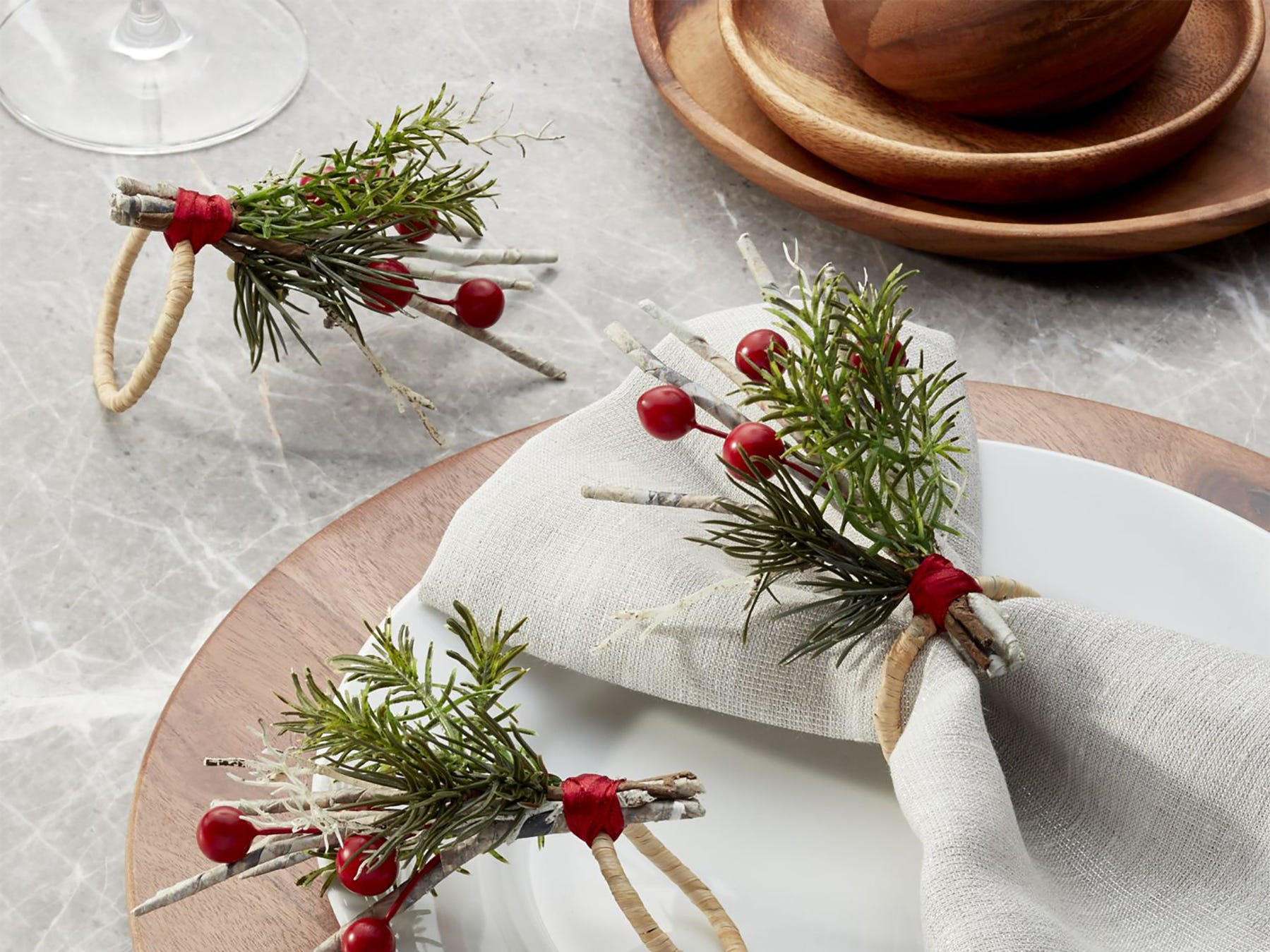 Springs of red berries, evergreens and white birch encircle these napkins. The napkin rings from Crate and Barrel are set on white plates over wooden chargers for a natural look.