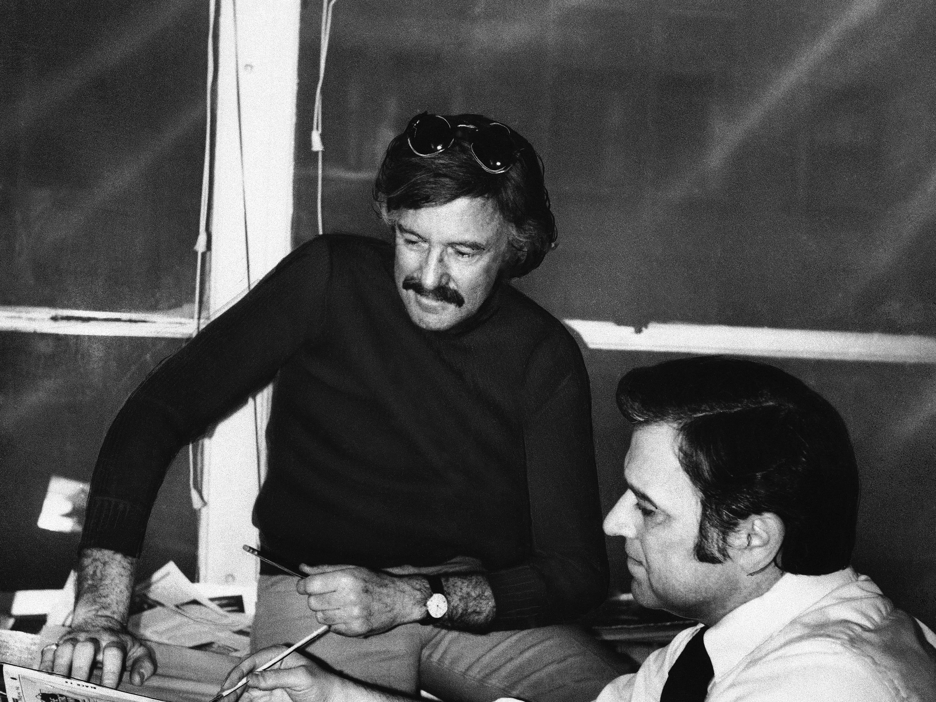 Stan Lee, in dark sweater, publisher and editor of Marvel Comics, and his art director, John Romita, look at a drawing in 1975 which will appear in one of the company's 85 different comic books, most of them monthly, most of them featuring superheroes, most written in college-level vocabulary.