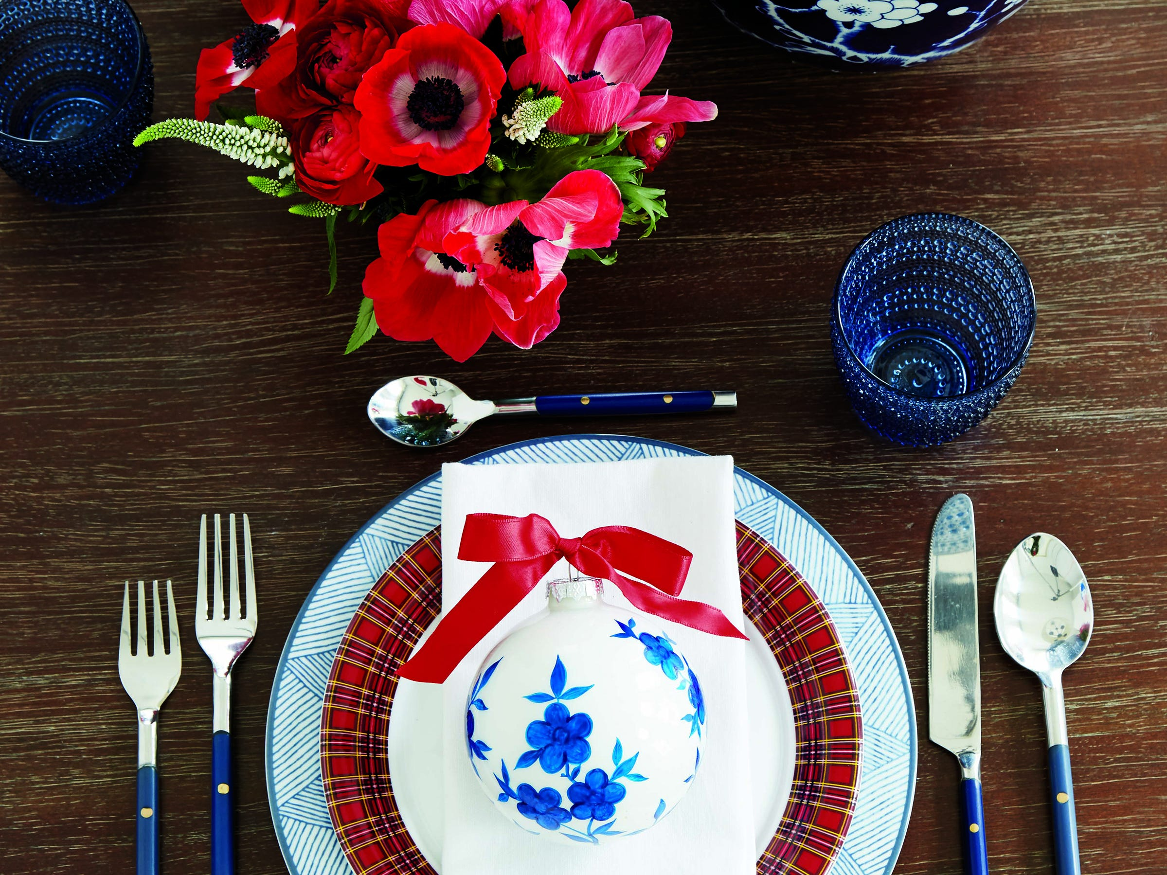 Suzanne Kasler strikes a cozy note with her teaming of a blue-and-white geometric plate from Bunny Williams with her own red plaid salad plate (from Ballard Designs), topped with a classic blue-and-white patterned ornament. She pulls the blue into flatware and glasses, and the red into amaryllis on the bare table. A touch of red whip stitching on pure white napkins adds a rustic note.
