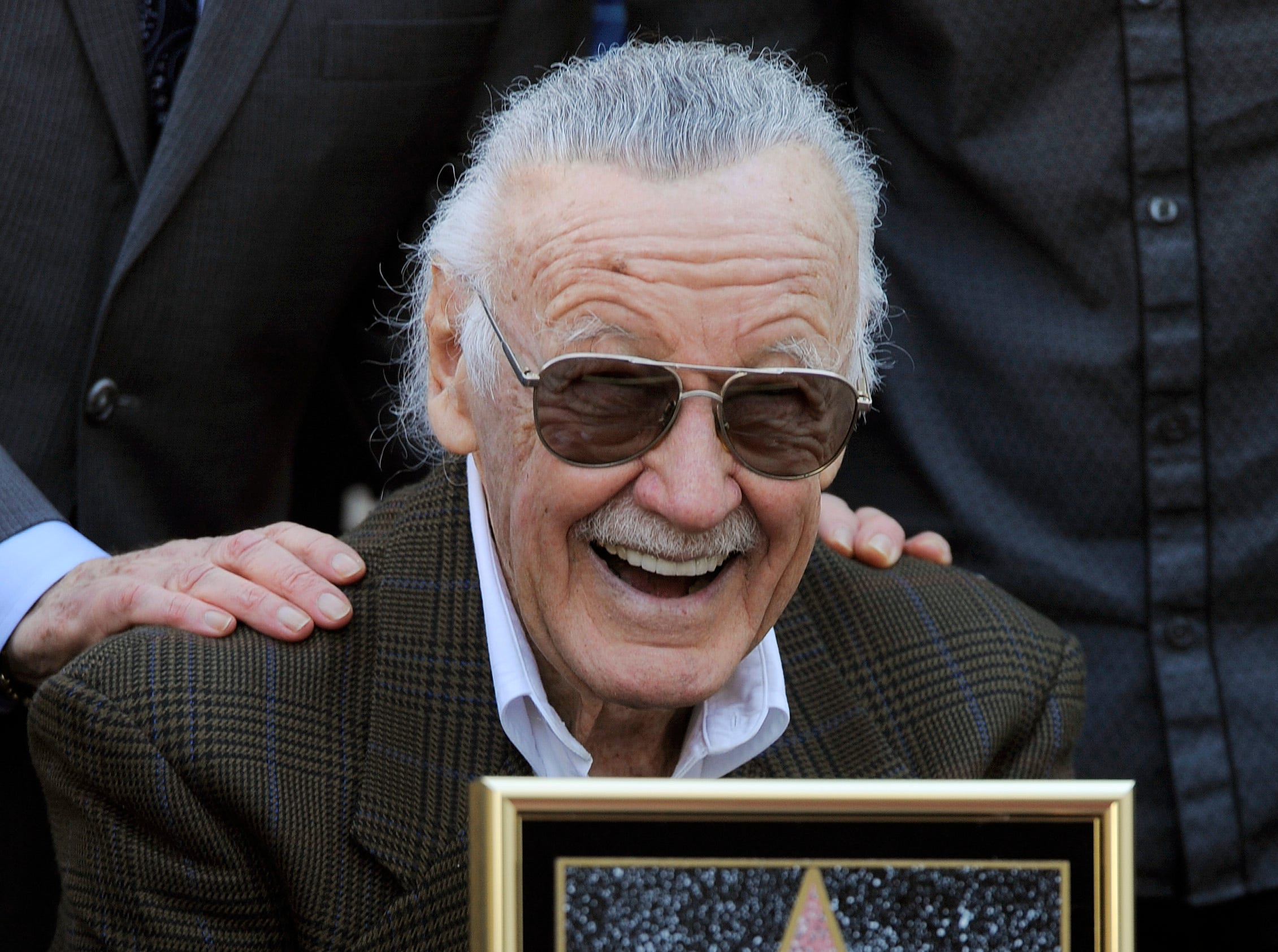Comic book creator Stan Lee poses with a replica of his new star on the Hollywood Walk of Fame in Los Angeles in 2011.