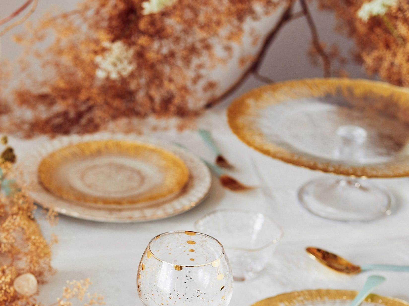 : A combination of gold-rimmed soda-lime glass with more rustic stoneware plates elegantly dress this table. The gold of the bordered Thistlewhit pieces beautifully blend with the russet tones in the decor. A surprise touch: gold Renscenca flatware with cool seafoam handles, all from Anthropologie.