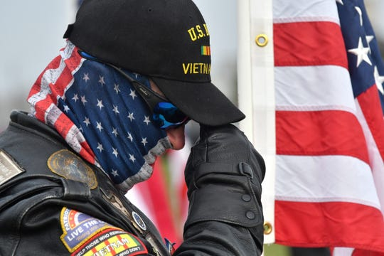 Howard Tibbits of the Patriot Guard Riders takes a private moment during the military ceremony at Great Lakes National Cemetery in Holly Monday.