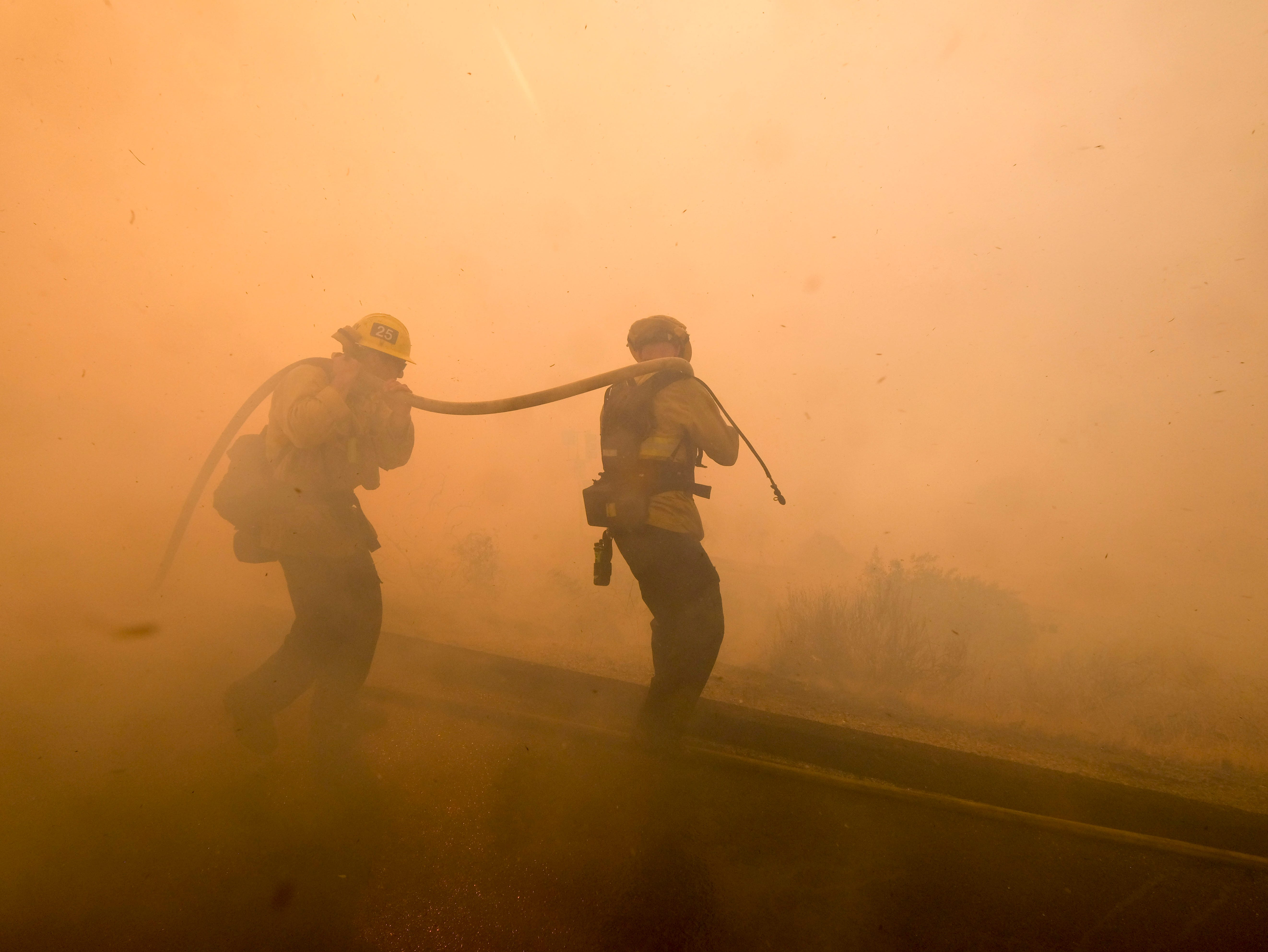 Firefighters battle a fire along the Ronald Reagan (118) Freeway in Simi Valley, Calif., Monday, Nov. 12, 2018.