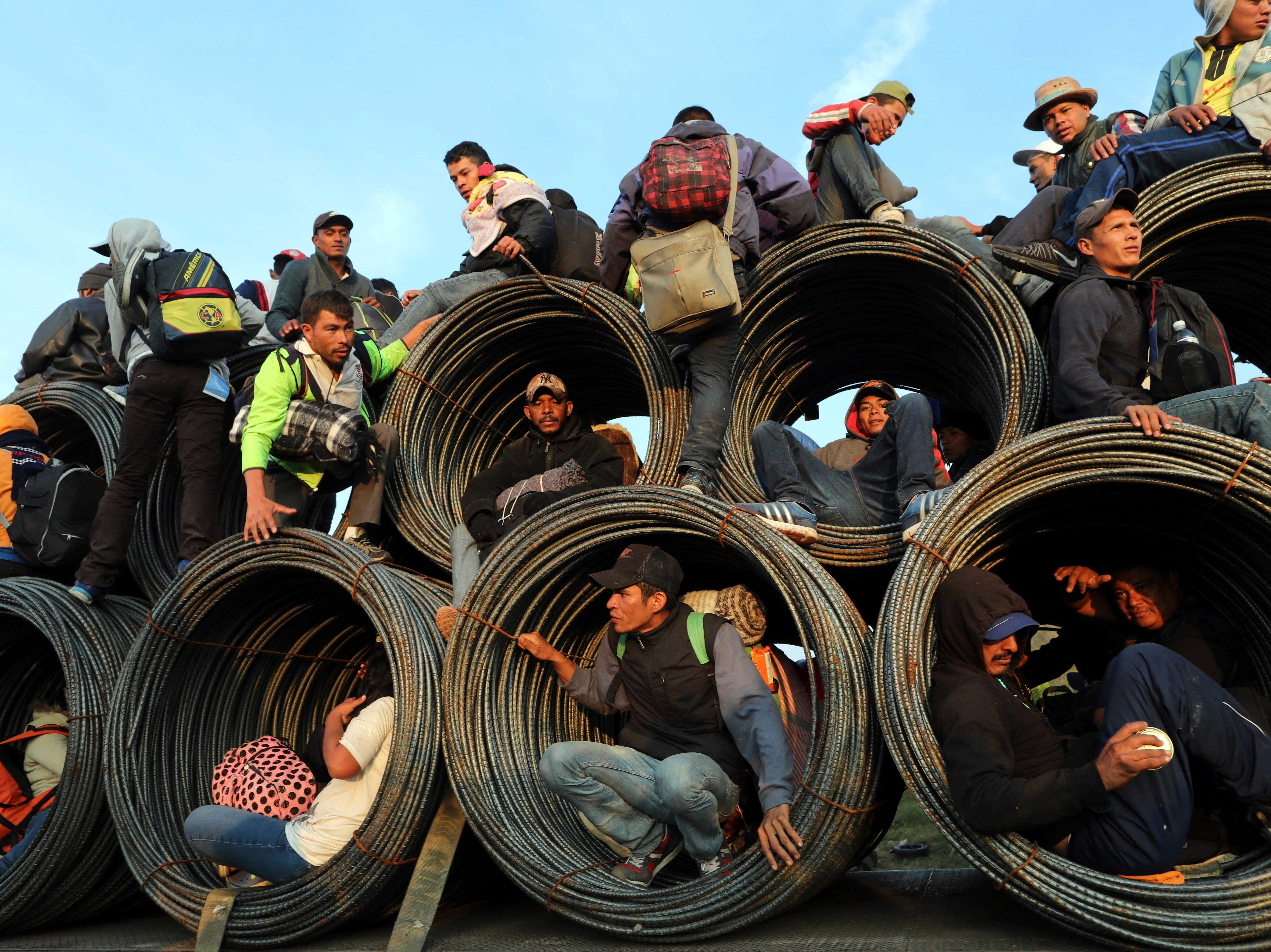 Central American migrants, part of the caravan hoping to reach the U.S. border, get a ride on a truck carrying rolls of steel rebar, in Irapuato, Mexico, Monday, Nov. 12, 2018. Several thousand Central American migrants marked a month on the road Monday as they hitched rides to the western Mexico city of Guadalajara and toward the U.S. border.