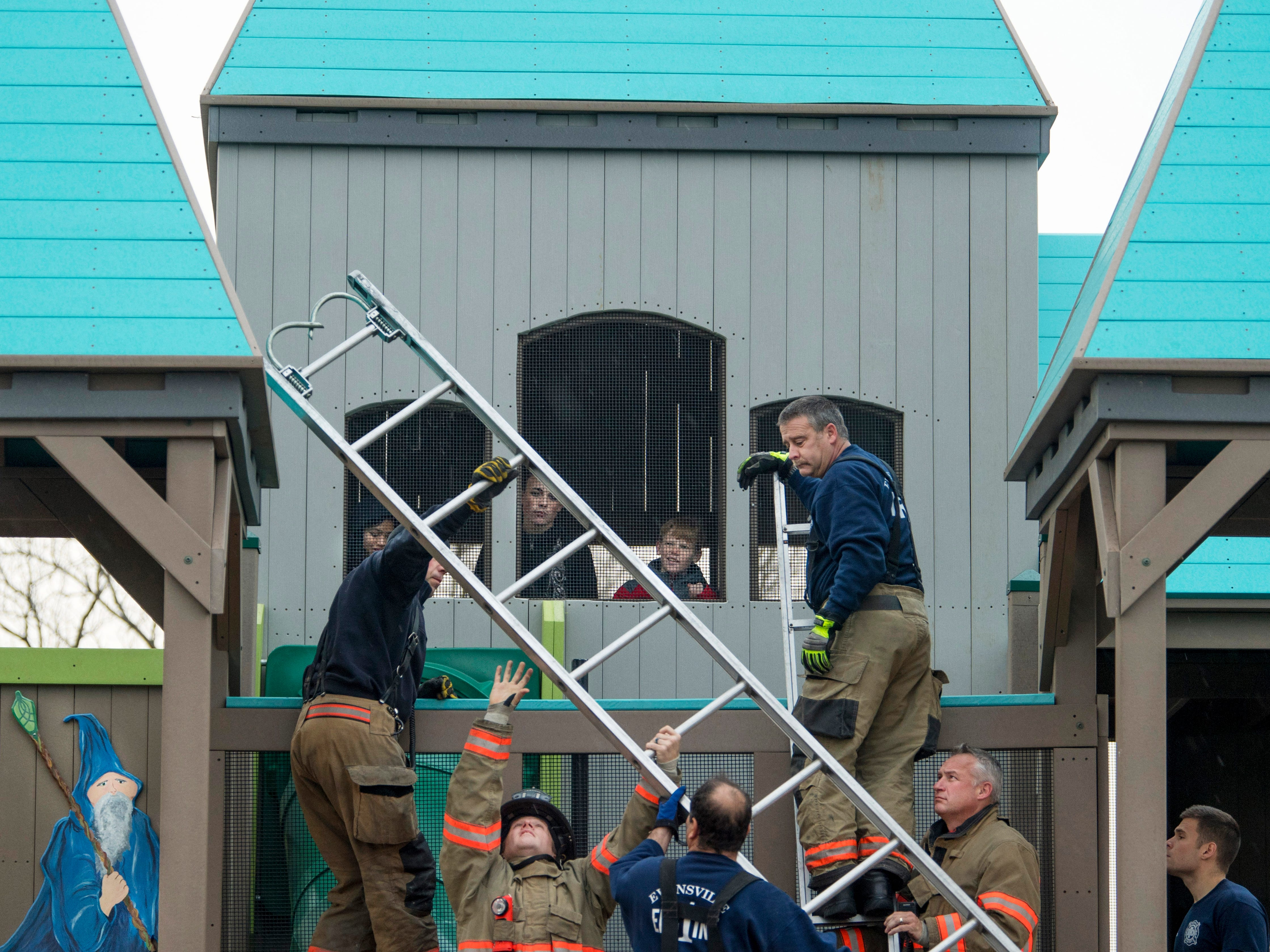 Evansville Fire Department rescue personnel with Fire Station No. 1 maneuver a ladder to rescue a 15-year-old boy who found himself trapped in a portion of the castle at Mickey's Kingdom Monday afternoon. The boy had climbed into an area that housed a tube slide but realized there was no way to escape without help. His friends stayed close to record the rescue with their cell phones.