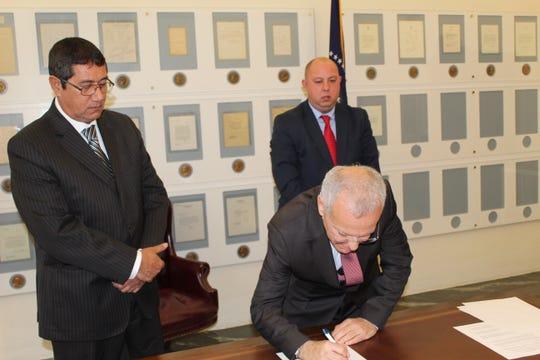 Paraguayan Ambassador German Rojas signs a sister city agreement linking Fremont with Villa Hayes, Paraguay, as Villa Hayes Mayor Esteban Rios Ayala, left, and Fremont Mayor Danny Sanchez,  look on.