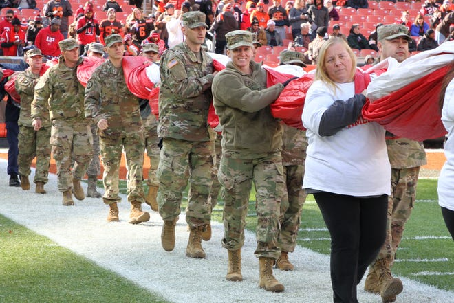 SFC Amanda Hise, in uniform at right, is followed by her husband 1st Lieutenant Matt Haszto as they help carry the U.S. flag onto the field at FirstEnergy Stadium in Cleveland on Sunday. They were among the veterans and active duty military personnel honored at the Browns game against Atlanta on Veterans Day.