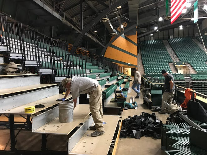 Workers with Rocky Mountain Construction and Coatings dismantle bleachers Monday on the west side of Moby Arena, where a new party deck will be built. School officials hope to have the deck, where fans will be able to purchase and drink beer during basketball and volleyball games, open by late January.