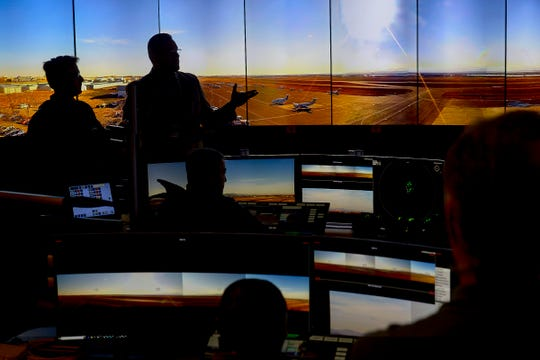 Airport manager Jason Licon, top right, shows a tour group the wall-sized array of monitors used for the airport's remote air traffic control tower on Nov. 9, 2018, at the Northern Colorado Regional Airport in Loveland.