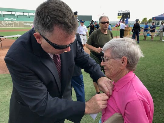 Norma Jock, 83, a 21-year service member in the Army and Navy, is presented her 50th Anniversary Vietnam War commemorative pin by Chris Crowley, a veteran of Operation Iraqi Freedom, and a Lieutenant Colonel in the Army Reserve Judge Advocate General Corps