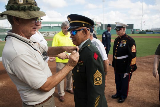 Army veteran Juan Cordero receives a Vietnam War Commemorative  Veterans pin at a ceremony at jetBlue Park on Wednesday. Cordero served two tours of duty in Vietnam as did McClure Mathews, behind him.