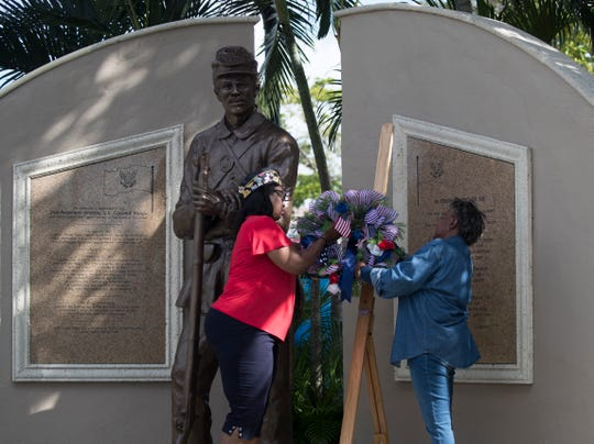 Andrea Grady, left, Ret. NC (Navy Counsel), and Commander of the Robert H.L. Dabney American Legion Post 192 in Fort Myers and Stephanie House, Veterans Affairs Committee Chair for the Lee County NAACP, lay a wreath during a Veteran's Day commemorative event at Centennial Park in Downtown Fort Myers, Monday, November 12, 2018. in front of the United States Colored Troops Memorial statue. The event, which was put together by the Lee County NAACP and 192nd American Legion Post, commemorated the recent restoration of the United States Colored Troops Memorial. The ceremony also marked the 20-year anniversary since the memorial was originally dedicated and unveiled on Veterans Day in 1998.