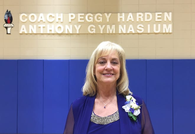 Former Pickens High volleyball coach Peggy Anthony stands in front of the plaque bearing her name Sunday following the dedication of the Coach Peggy Harden Anthony Gymnasium.