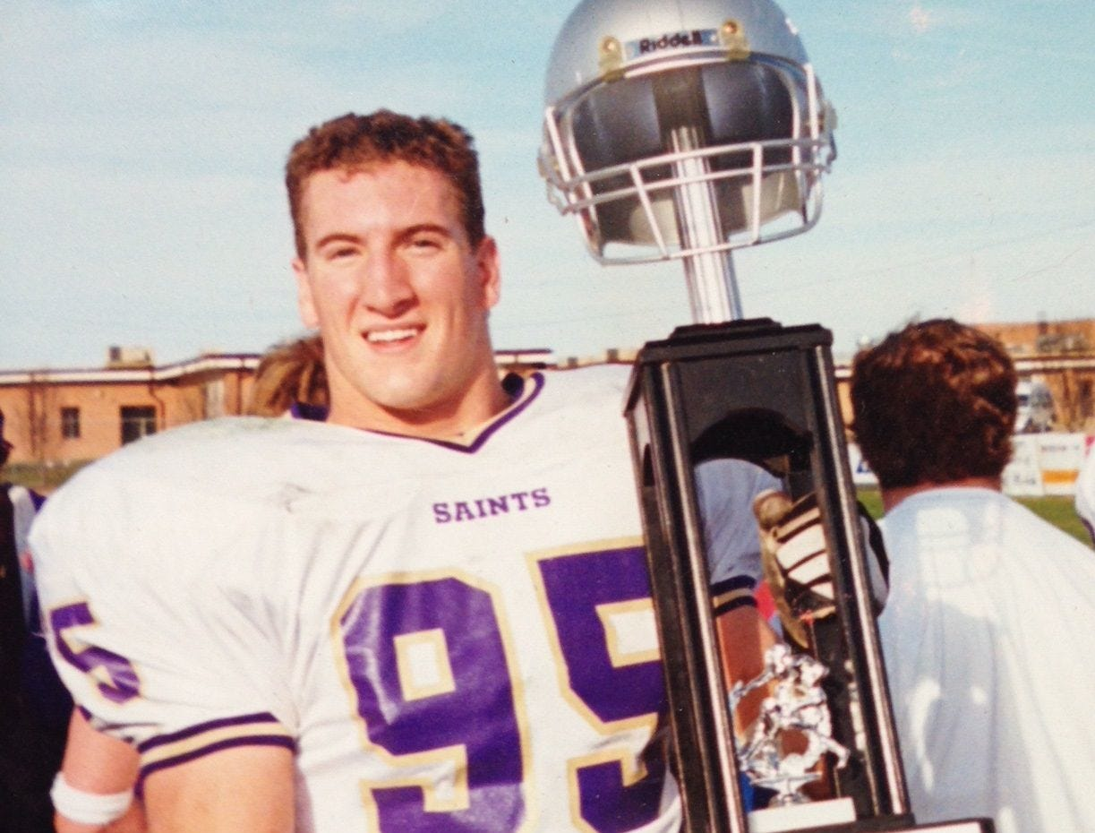 Centerville's Jeff Shirley, then playing for Carroll College, holds the NAIA National Championship trophy after the Saints won the title in 2002, his freshman year.