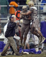 Carroll College head coach Mike Van Diest, left, celebrates a defensive stop along with Will Hamilton (98) and Mike Paffhausen (72) during the fourth quarter of the NAIA Championship football game against University of Sioux Falls, in Savannah, Tenn., Saturday, Dec. 15, 2007.  Carroll won 17-9.