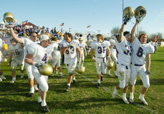Carroll College of Montana players celebrate their 28-7 victory over Georgetown College in the NAIA championship game in Savannah, Tenn., Saturday, Dec. 21, 2002.