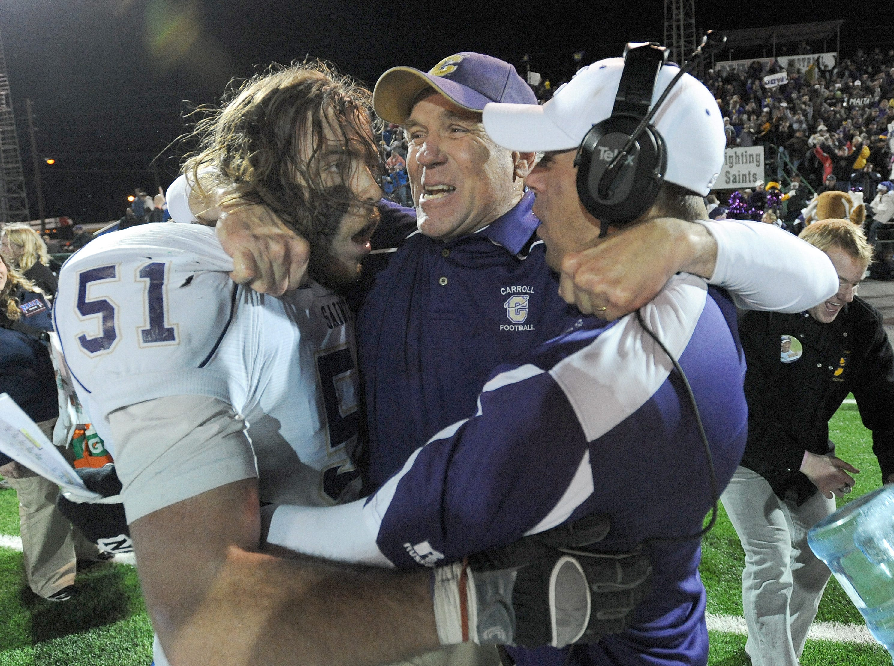 Carroll College coach Mike Van Diest, center, is hugged by linebacker Lynn Mallory and another coach after Carroll College defeated Sioux Falls in the NAIA college football championship game at Brannon Field on Dec. 18, 2010, in Rome, Ga.