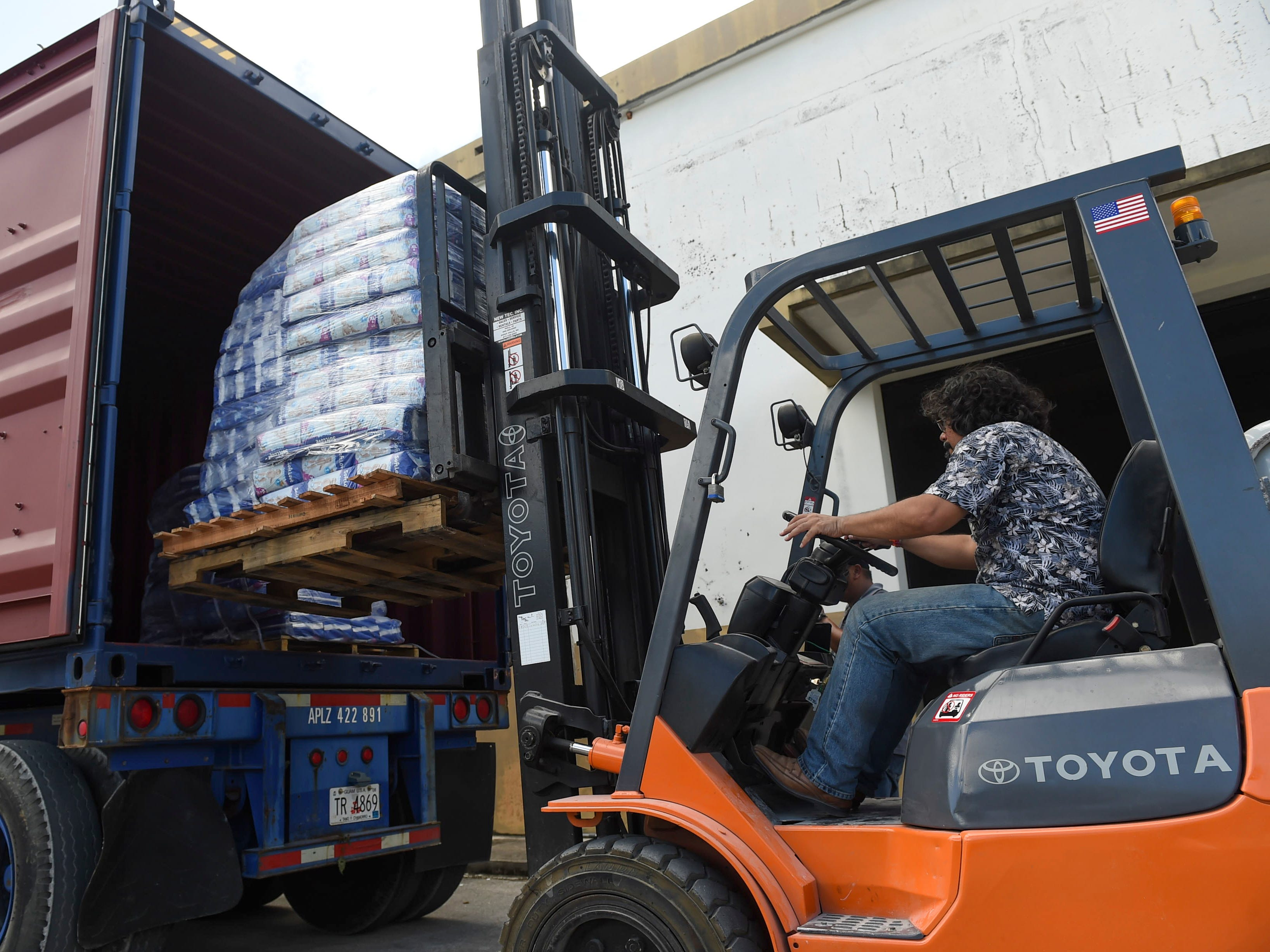 Asia Pacific Wholesalers owner Deepak Dewan uses a forklift to load a pallet of baby diapers into a container of donations for the CNMI at their warehouse in Dededo, Nov. 12, 2018.