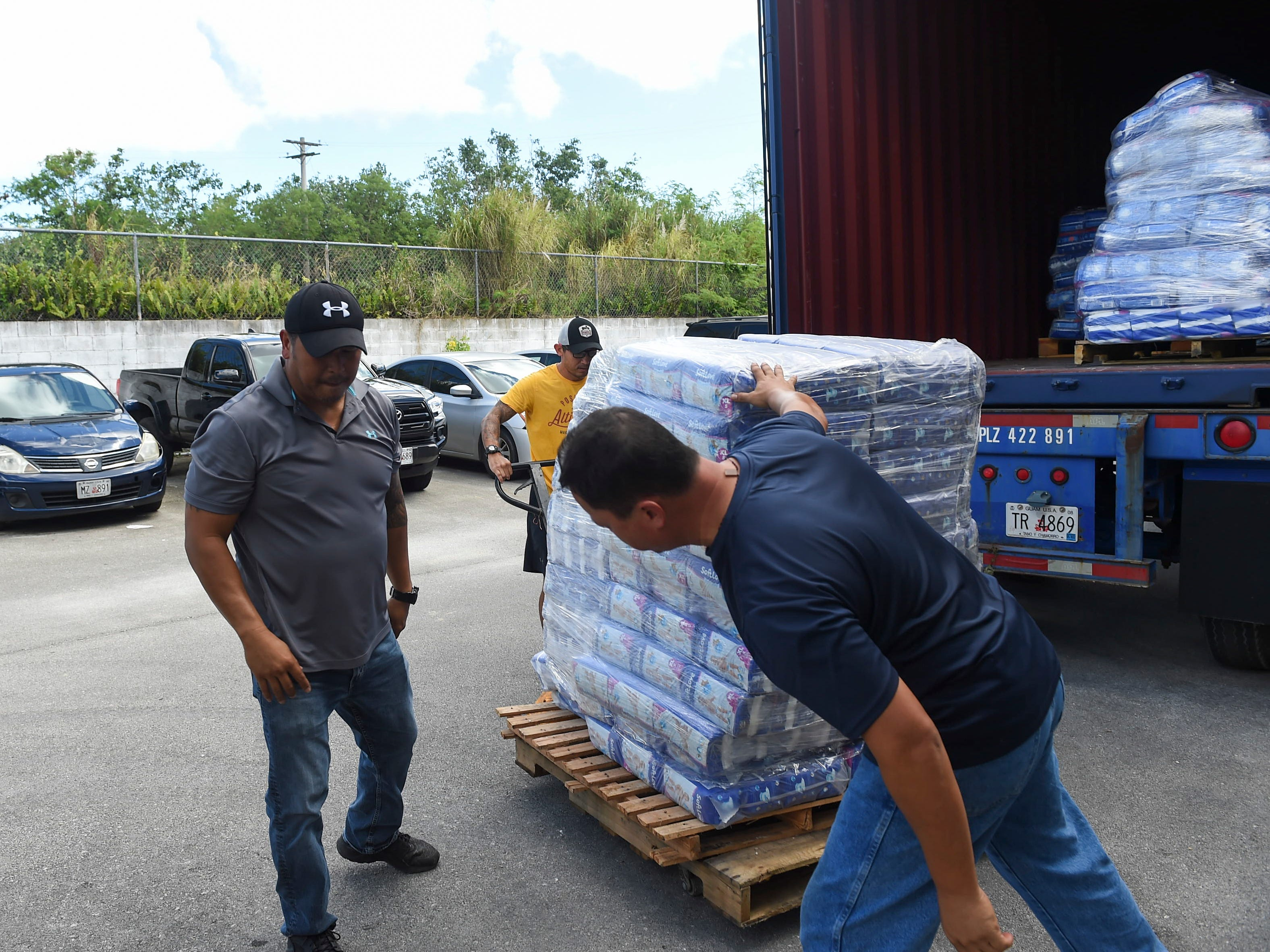 Asia Pacific Wholesalers General Manager Peter Aguon, left, Delta Tire and Lube employee Gerry Gutierrez, center, and Delta Tire and Lube General Manager Jerry Francisco help transport pallets of donations for CNMI residents at the Asia Pacific Wholesalers warehouse on Nov. 12, 2018.