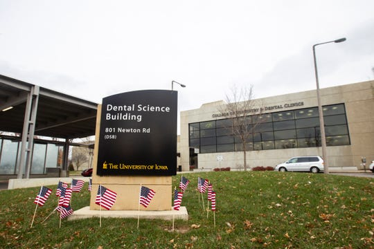 American flags surround the sign for the Dental Science Building at on Monday, Nov. 12, 2018, at 801 Newton Rd on the University of Iowa campus in Iowa City.