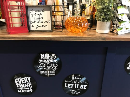 Signs about coffee and music are shown inside Good Vibe Cafe in Solon on Nov. 12, 2018.