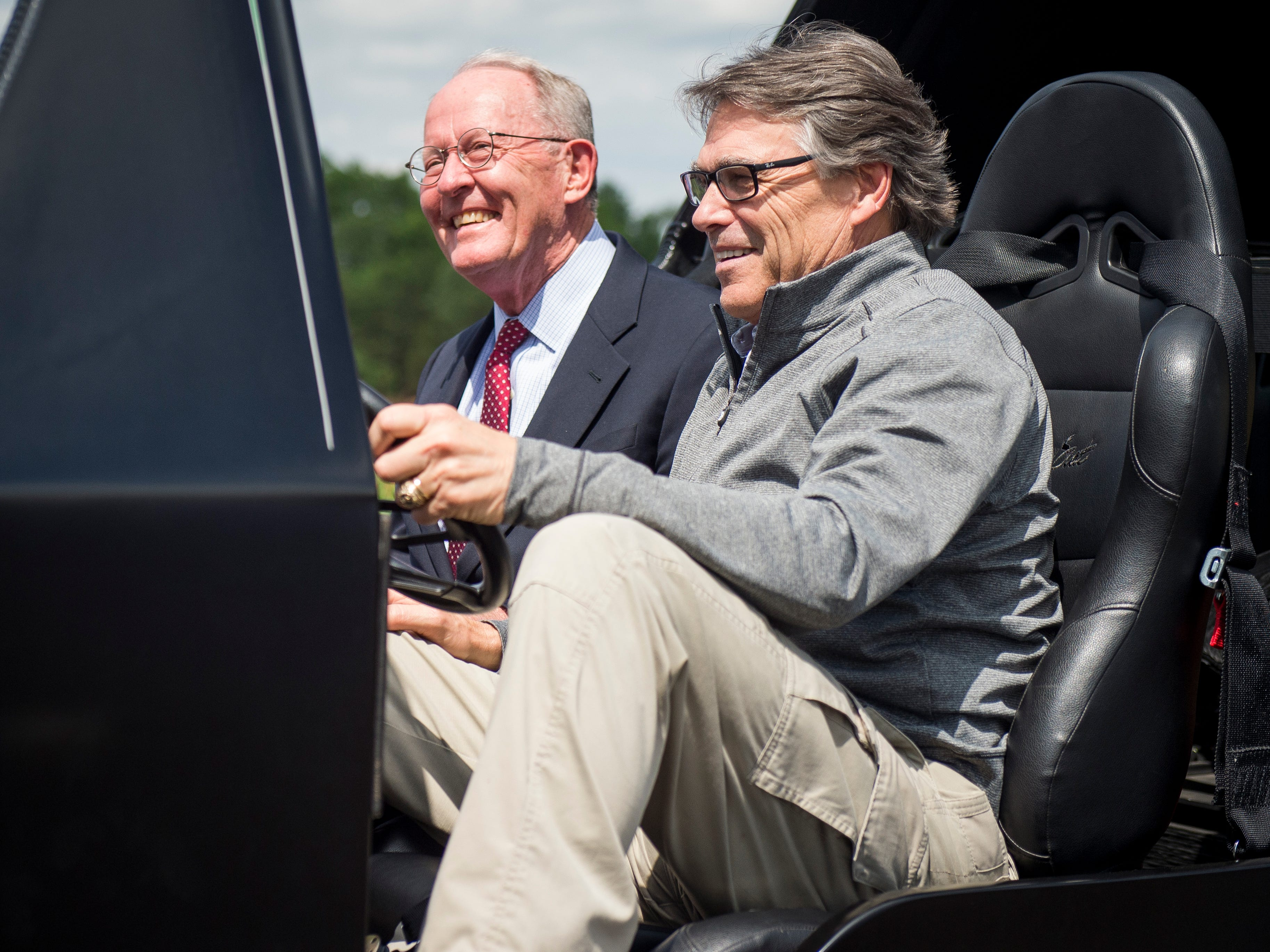 Secretary of Department of Energy Rick Perry, right, and U.S. Sen. Lamar Alexander, left, sit in a 3D-printed vehicle during a tour of Oak Ridge National Laboratory's Manufacturing Demonstration Facility on Monday, May 22, 2017.
