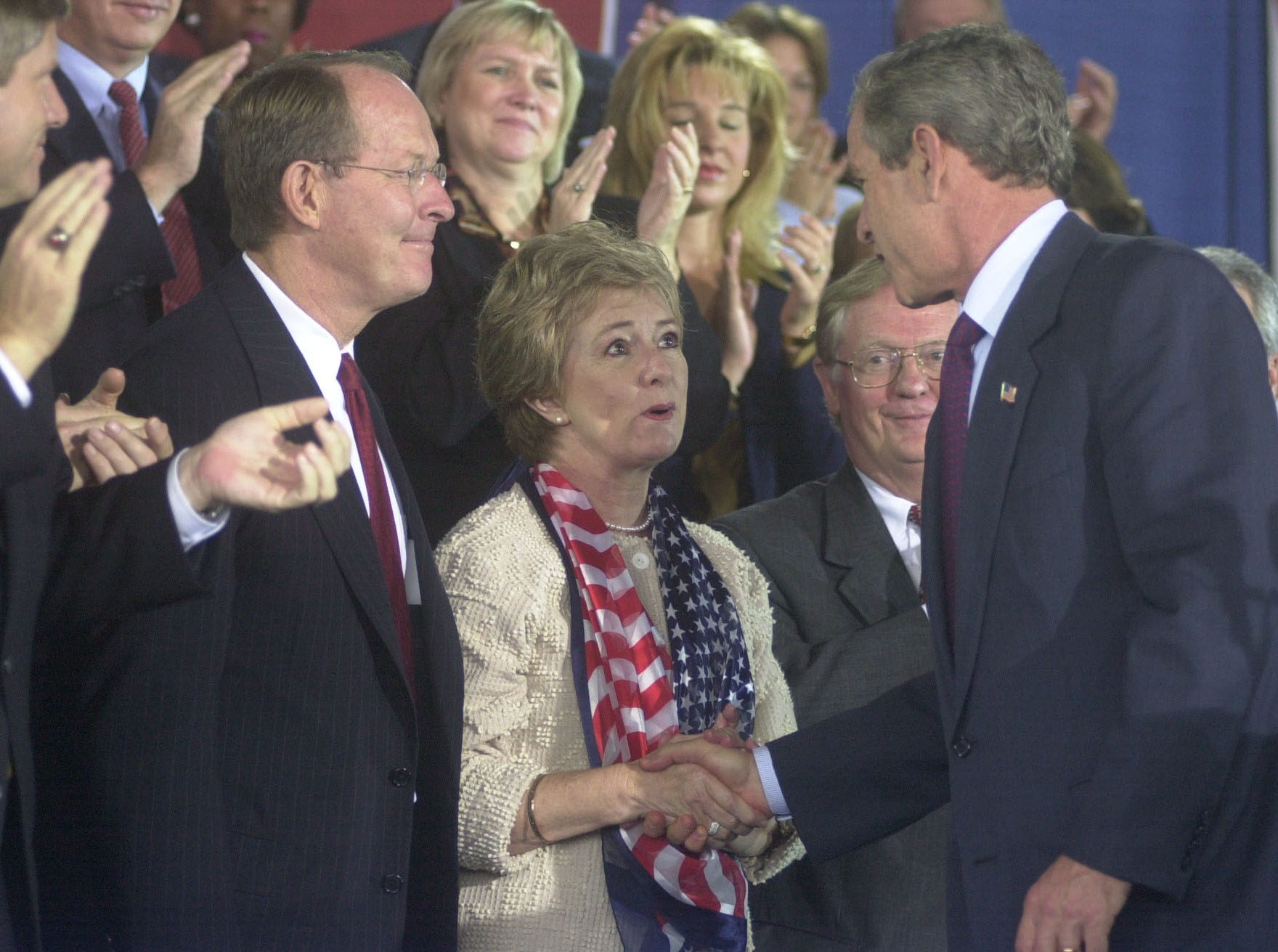 President George W. Bush greets Janice Bowling, center, and Lamar Alexander, left, at the Cherokee Aviation Hangar in Alcoa, Tenn., Tuesday, October 8, 2002 during an appearance where he addresses  the public.