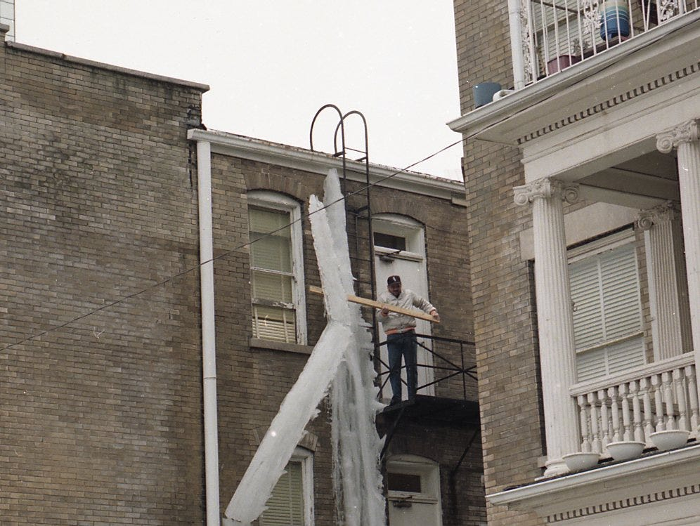 Victor Lenoir knocks down a giant icicle that formed on the rear of the Elliott Hotel on Church Street during a cold spell in February 1996.