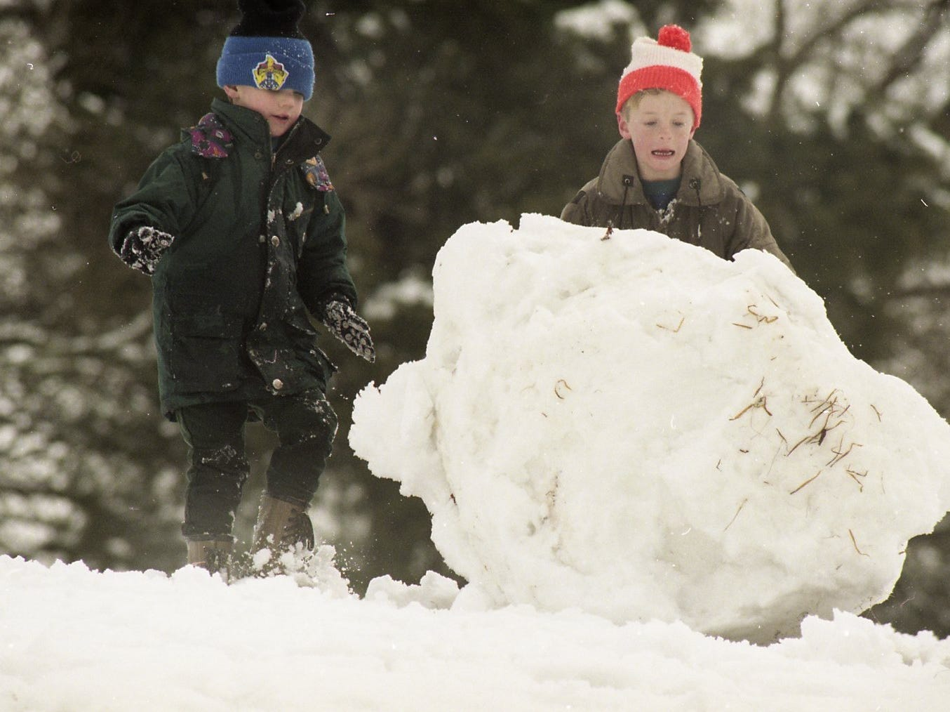 Cory Wright, 5, and his friend Robert Fisher, 7, roll a large snow ball down the hill in Concord Park in West Knoxville in January 1996. The boys struggled with their oversized snowball even with down hill gravity on their side.